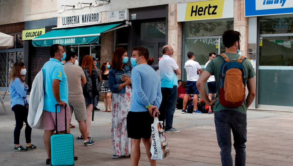 Varias personas hacen cola ante una central de Hertz ubicada en las inmediaciones de la estación de Sants de Barcelona