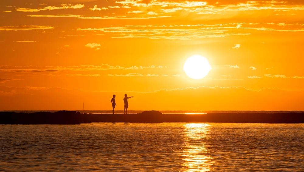 Unos bañistas contemplan el atardecer desde la barra natural de la playa de Las Canteras, en Las Palmas de Gran Canaria