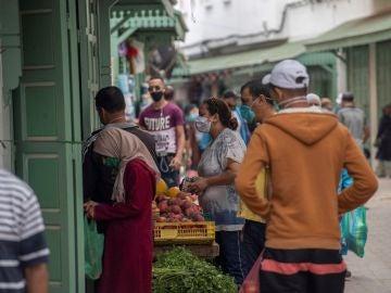 Varias personas con mascarillas compran fruta en Rabat (Marruecos)