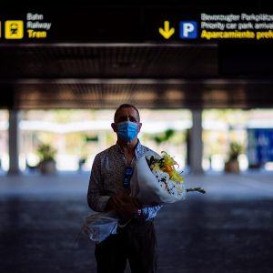 Un hombre espera la llegada de su pareja en el aeropuerto de Málaga-Costa del Sol