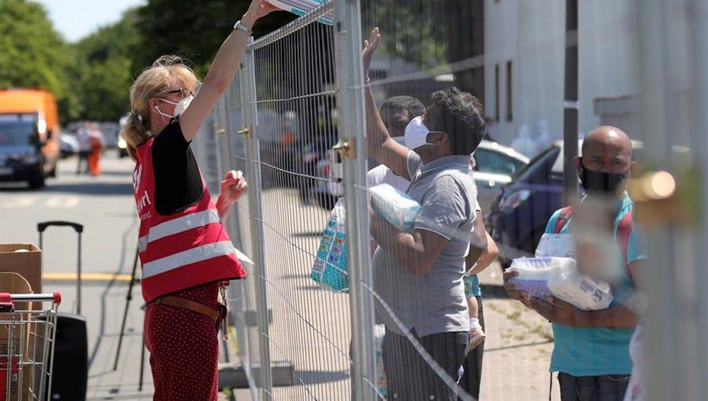 Una empleada municipal distribuye pañales a personas en cuarentena en el barrio