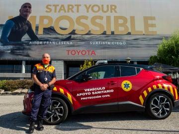 Un voluntario de Protección Civil posa junto al vehículo cedido por Toyota