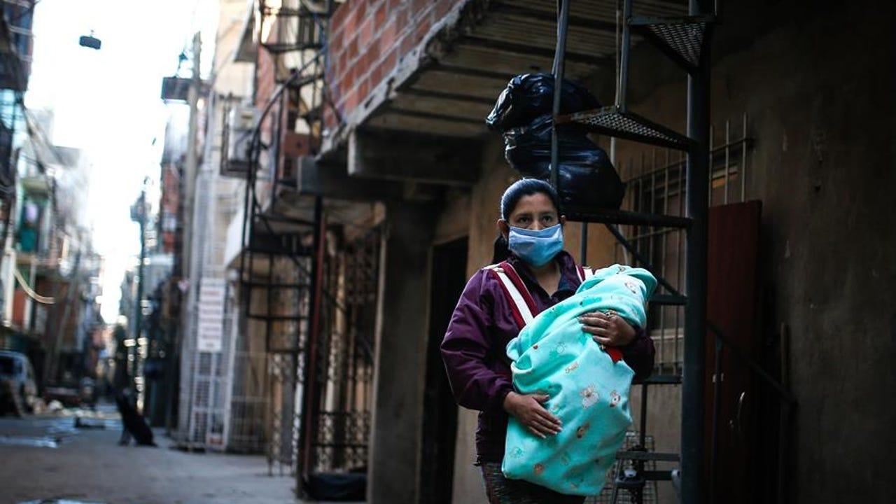Una mujer con mascarilla lleva a su bebé por una calle de la Villa 31, Buenos Aires