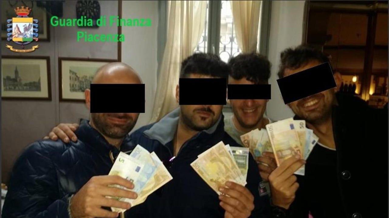 Imagen facilitada por la Guardia de Finanzas de cuatro de los carabineros arrestados mostrando dinero.