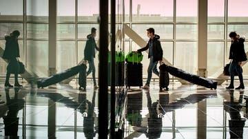 Varios pasajeros protegidos con mascarillas en el aeropuerto de Barcelona