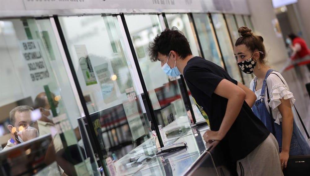 Dos personas compran billetes para viajar en autobús en la Estación Sur de Madrid