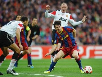 Rio Ferdinand y Wayne Rooney enciman a Leo Messi