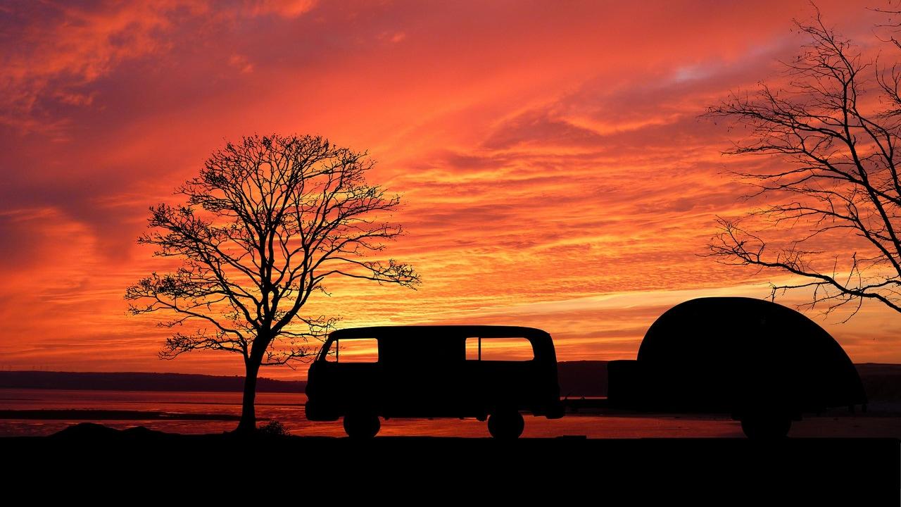 Imagen de una caravana en un rojo atardecer