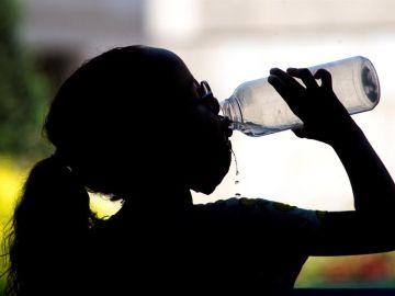 Una niña bebe agua en el centro de Ourense, en alerta por altas temperaturas