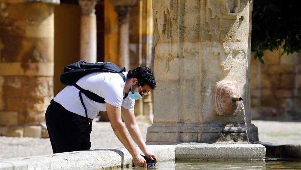 Un hombre se refresca en una fuente de Córdoba