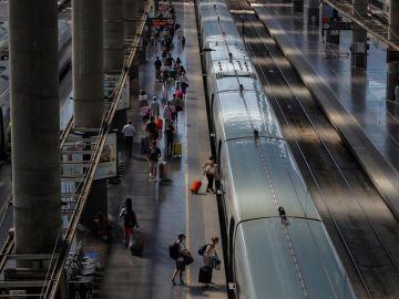 Varias personas suben al AVE en la Estación de Atocha en Madrid.