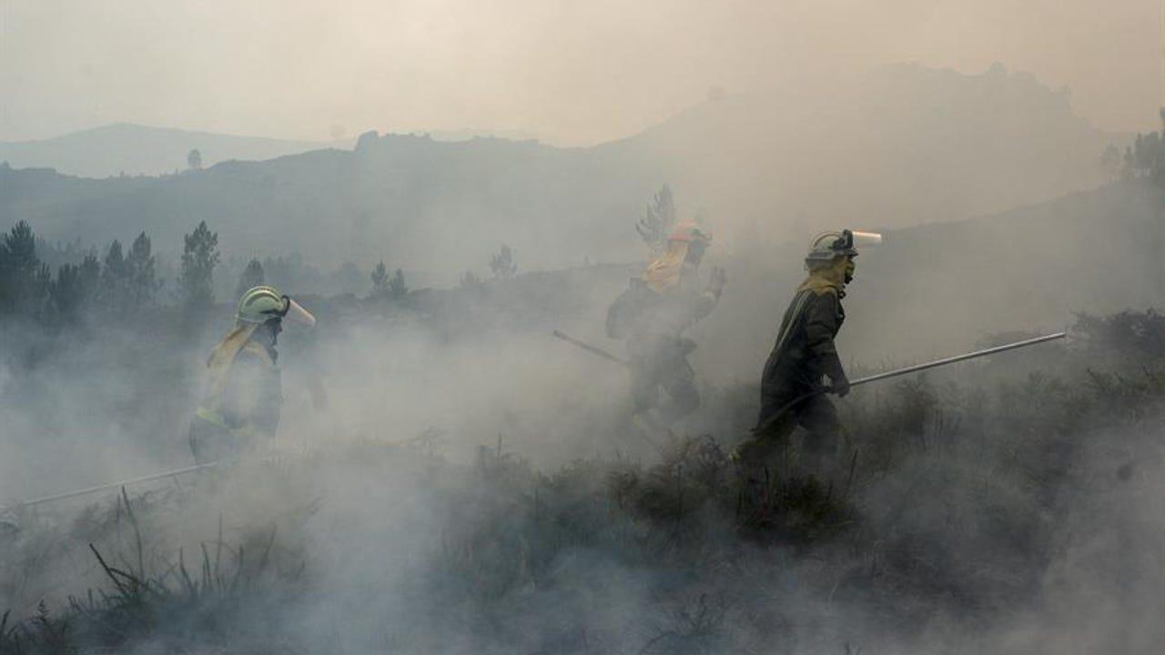 Efectivos de las brigadas contra incendios trabajan en las labores de extinción del fuego en el transfronterizo Parque del Gerês-Xurês.