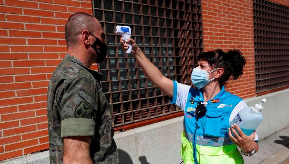 Una sanitaria toma la temperatura a un militar antes de realizarse una PCR en Villaverde