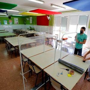 Dos docentes colocan los separadores en el comedor de un colegio