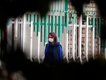 Una mujer pasea por las calles de Teherán con mascarilla