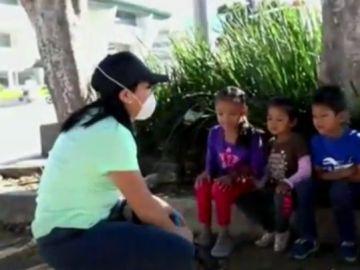 Imagen de una maestra dando clase en la calle a niños sin recursos de México