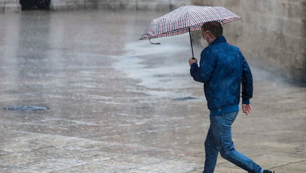 Una persona se protege de la lluvia con paraguas en el centro de Valencia