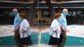 Una pareja pasea con mascarillas