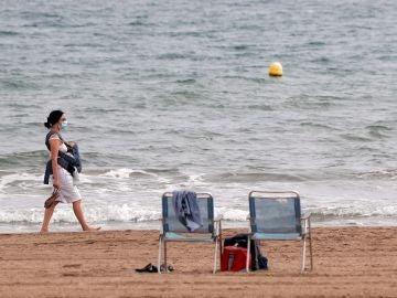 Imagen de una mujer paseando por la playa de la Malvarrosa