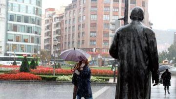 Varias personas se protegen de la fuerte lluvia en Bilbao
