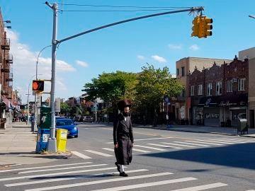 Un judío ultraortodoxo cruza una calle, sin llevar mascarilla, en el condado de Brooklyn
