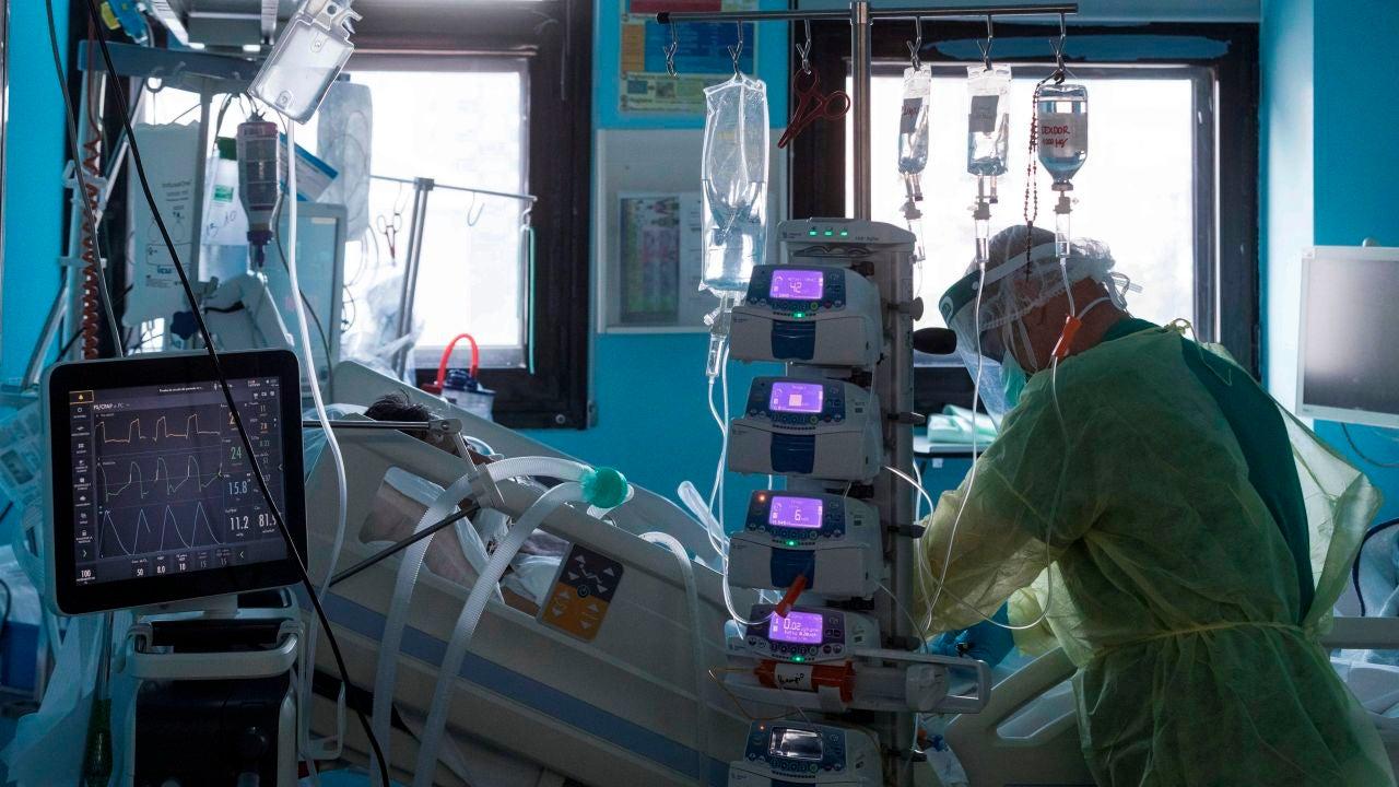 Un enfermero del centro hospitalario atiende a un paciente ingresado por COVID-19 en la UCI