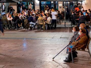 Imagen de una plaza del centro de Oviedo con una cafetería llena de clientes