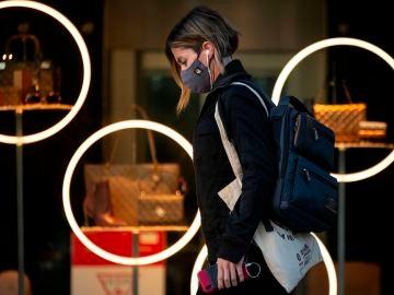 Una mujer con mascarilla pasea por Paseo de Gracia, en Barcelona