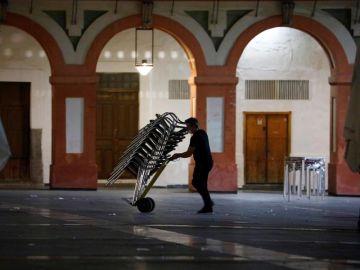 Un camarero recoge la terraza de su bar en Córdoba