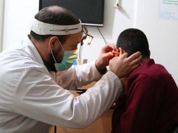 Un médico ausculta el oído de un paciente.