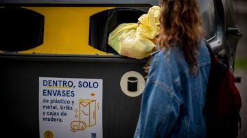 Una mujer tira una bolsa de basura al contenedor amarillo