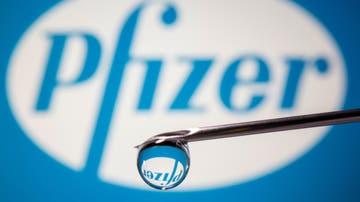 El logo de Pfizer, visto a través de una gota