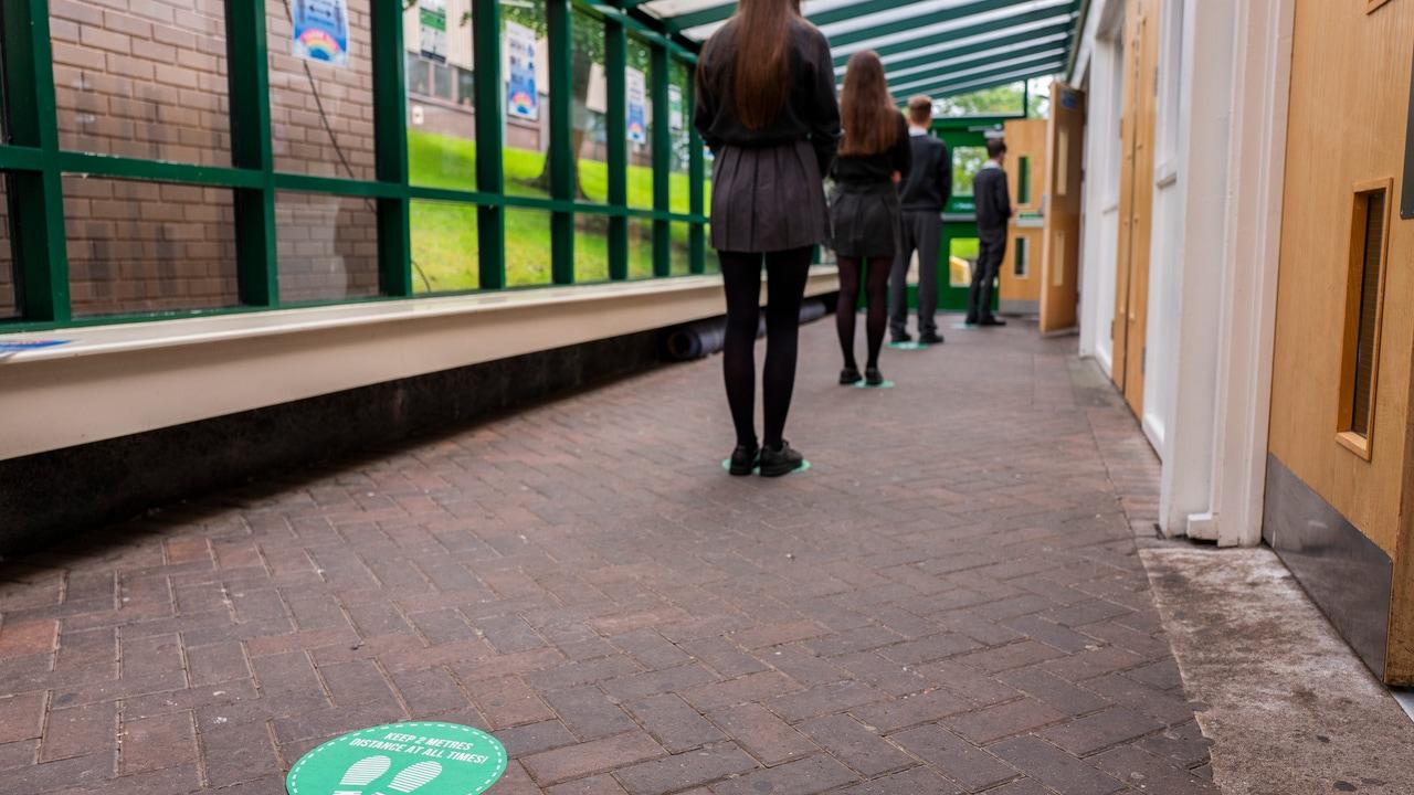 Alumnos de un colegio hacen cola antes de entrar a clase.