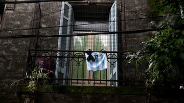 Un balcón con una camiseta de Maradona y un crespón negro
