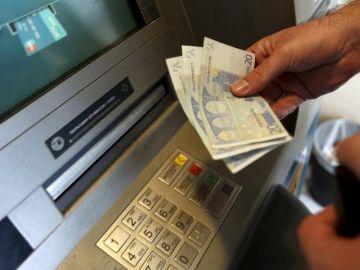 Una mujer saca dinero de un banco