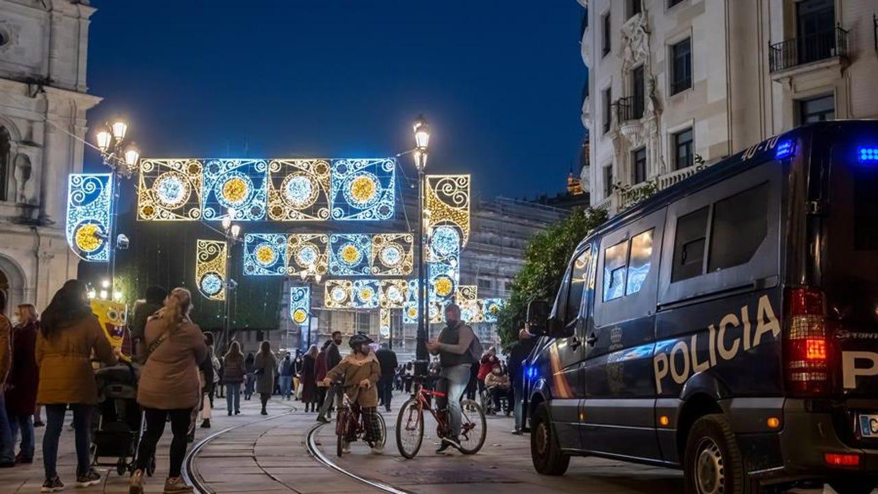 Varias personas caminan por una calle iluminada con motivo de la Navidad en Sevilla.