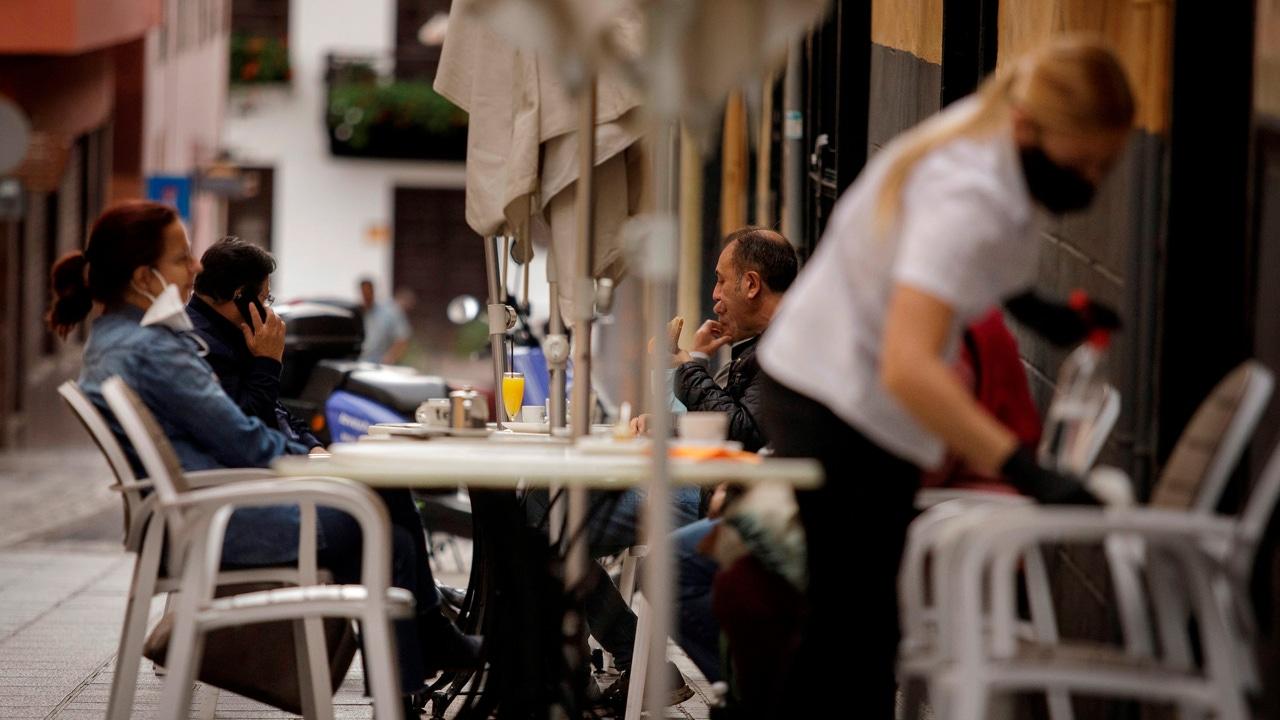 Una camarera de una cafetería de Santa Cruz de Tenerife limpia una mesa mientras varios clientes consumen en la terraza