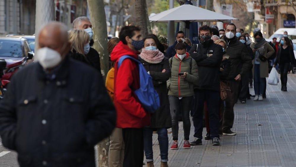 Numerosas personas hacen cola para hacerse test de antígenos en un laboratorio privado de Barcelona.