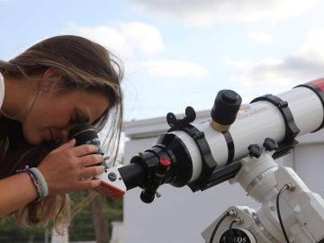Una chica observa a través de un telescopio.
