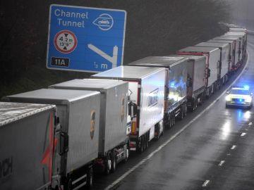 Un coche de policía pasa junto a una larga cola de camiones que permanecen atrapados a causa del cierre de la frontera con Reino Unido.
