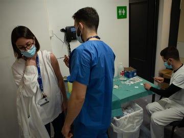Profesionales sanitarios preparan y administran la vacuna de covid-19 a sus compañeros en el Hospital Vall d'Hebrón de Barcelona.