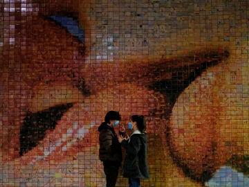 Una pareja pasea por Barcelona con mascarilla