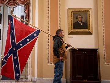 Uno de los asaltantes del Capitolio porta la bandera confederada