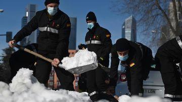Varios efectivos limpian una calle tras las fuertes nevadas causadas por el temporal Filomena en Madrid.