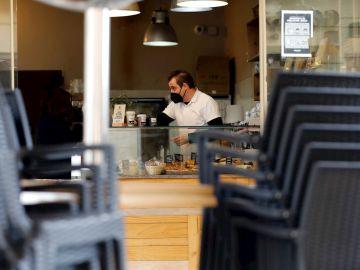 Un hostelero prepara cafés para llevar en una cafetería