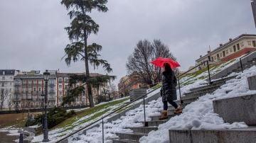 Una viandante baja una escalinata cerca del madrileño Museo del Prado bajo la lluvia, este miércoles