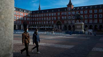 Personas con mascarilla caminan por la Plaza Mayor de Madrid