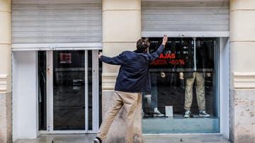 El trabajador de un comercio cierra su establecimiento el primer día del cierre total de la hostelería en Valencia