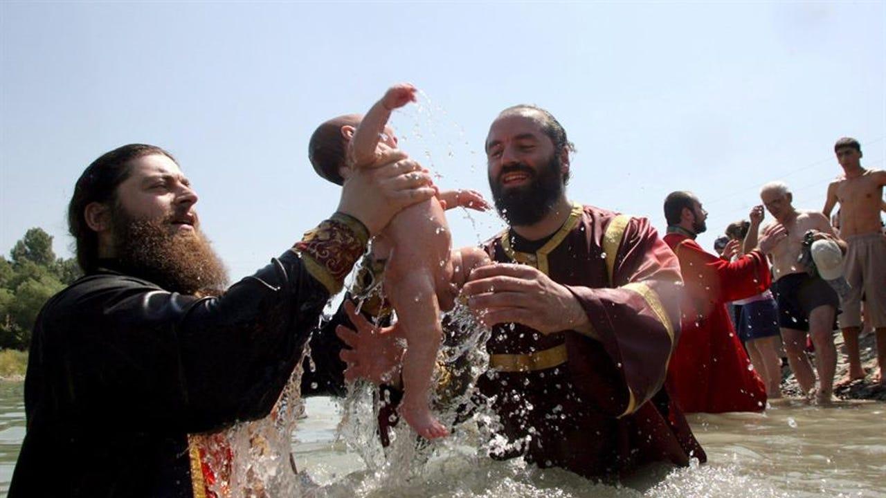 Dos sacerdotes ortodoxos georgianos sostienen un niño durante una ceremonia de Bautismo
