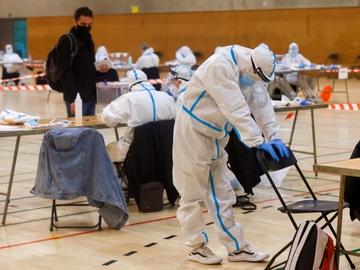 Varias personas vestidas con equipos de protección individual (EPI) en las elecciones catalanas